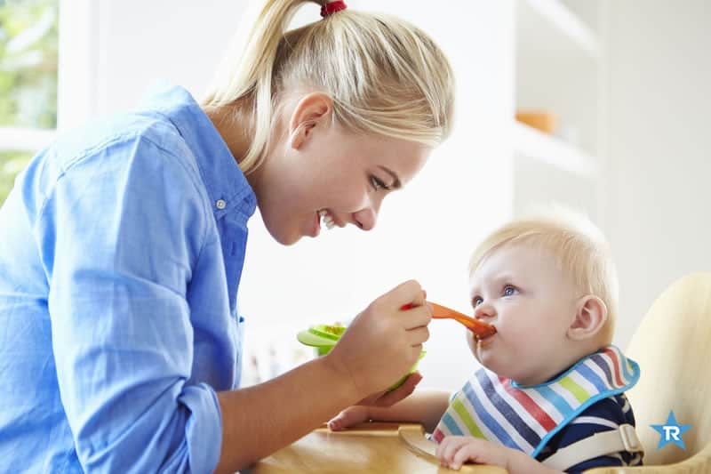 mother feeding baby boy with diy baby food